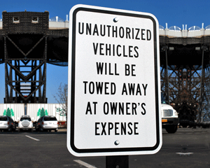 Unauthorized vehicles towed away sign