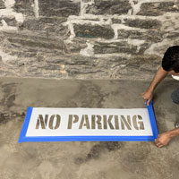Taping around a no parking stencil